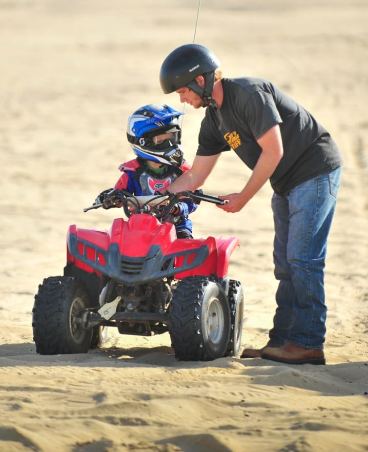 Staff teaching child how to ride an ATV at Pismo Beach