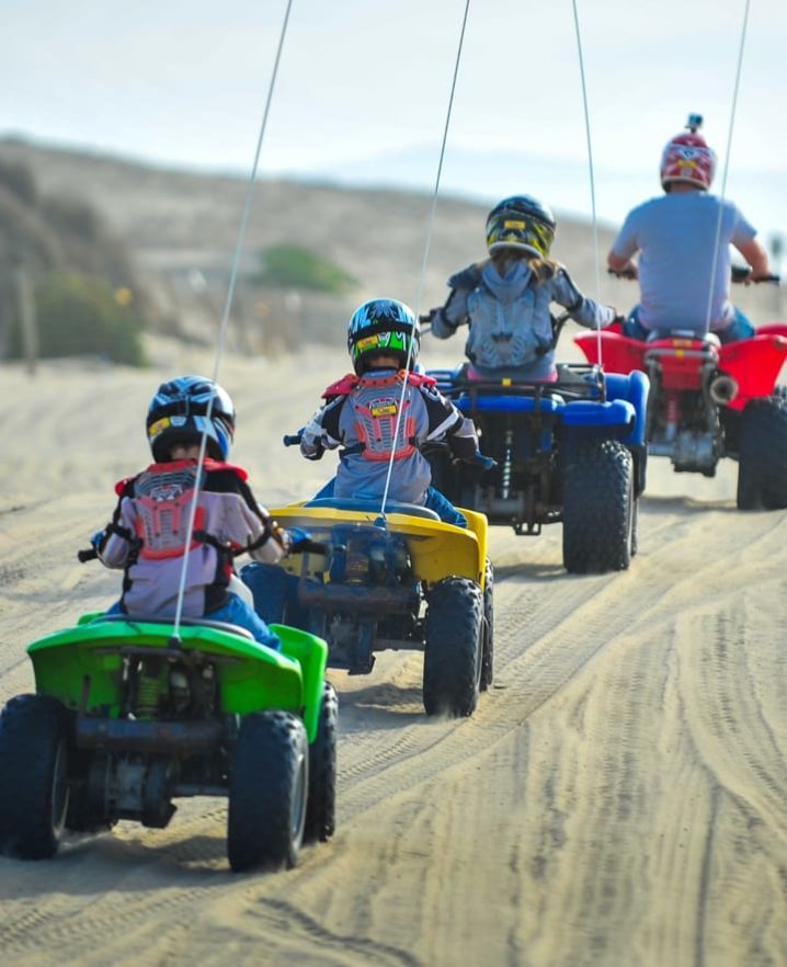 Family riding ATVs at Pismo Beach