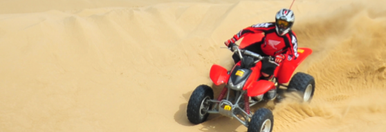 Guest riding at ATV through sand dune