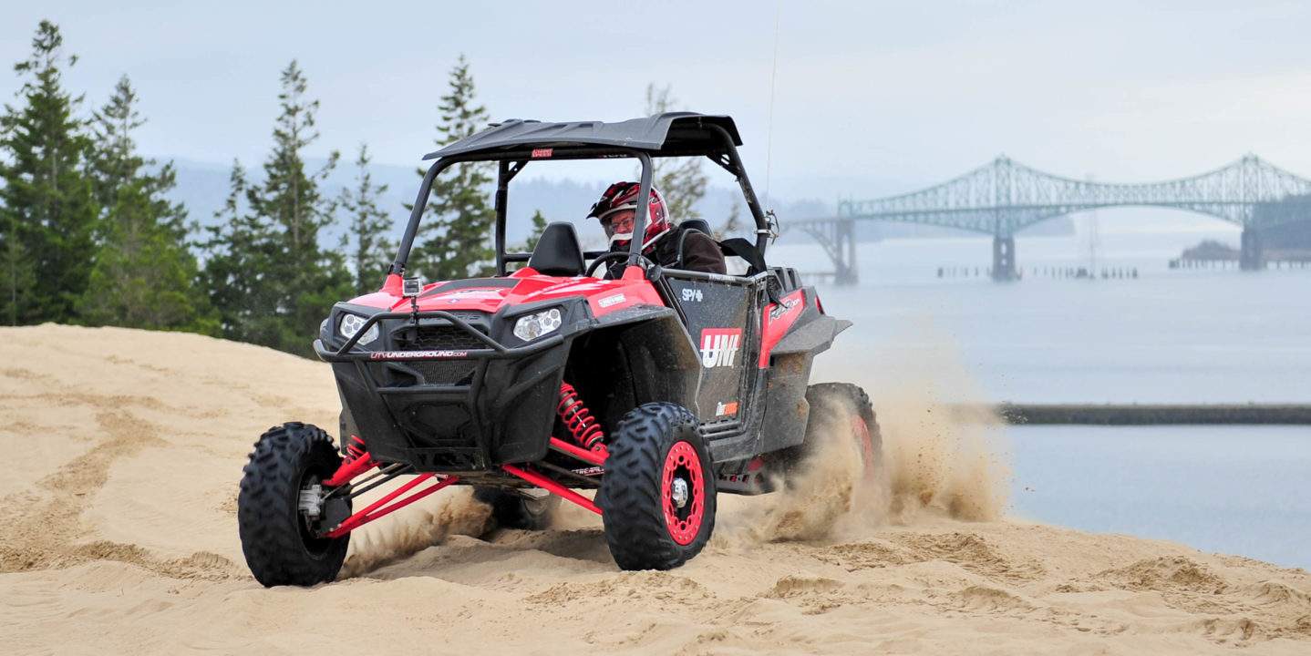 Man riding an ATV in Oregon Dunes by ocean and bridge