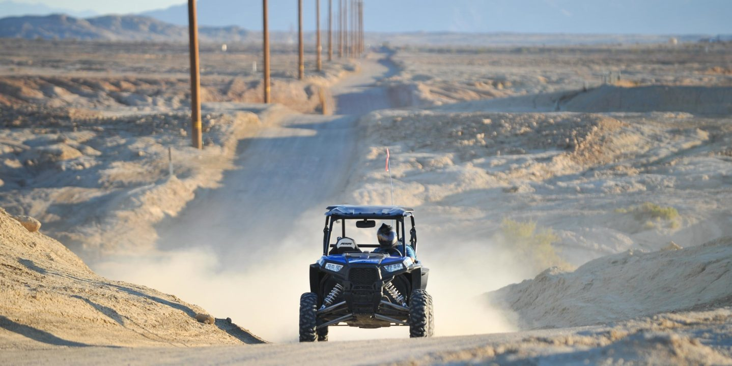 Two guests riding in ATV on a long dirt road