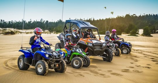 Children and adults riding ATVs
