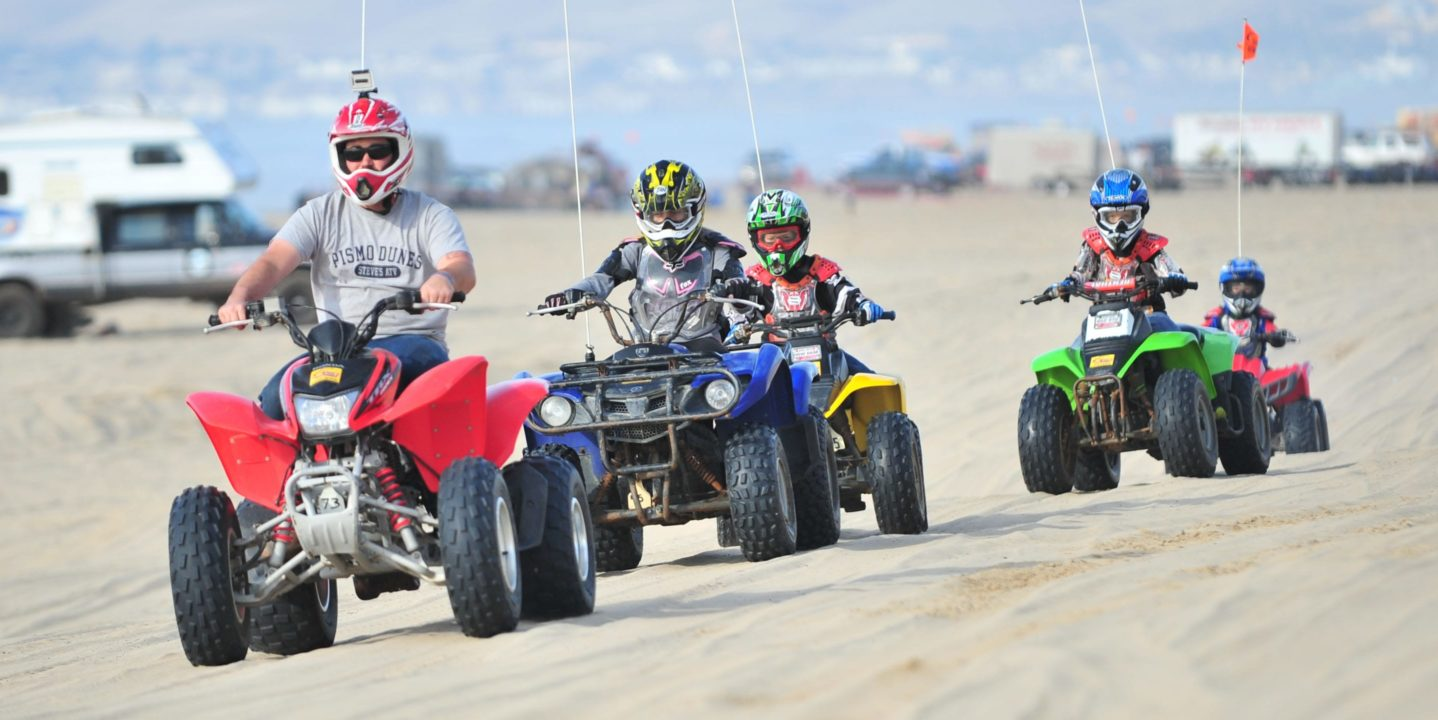 Family riding on different colored ATVs at Pismo Beach, CA