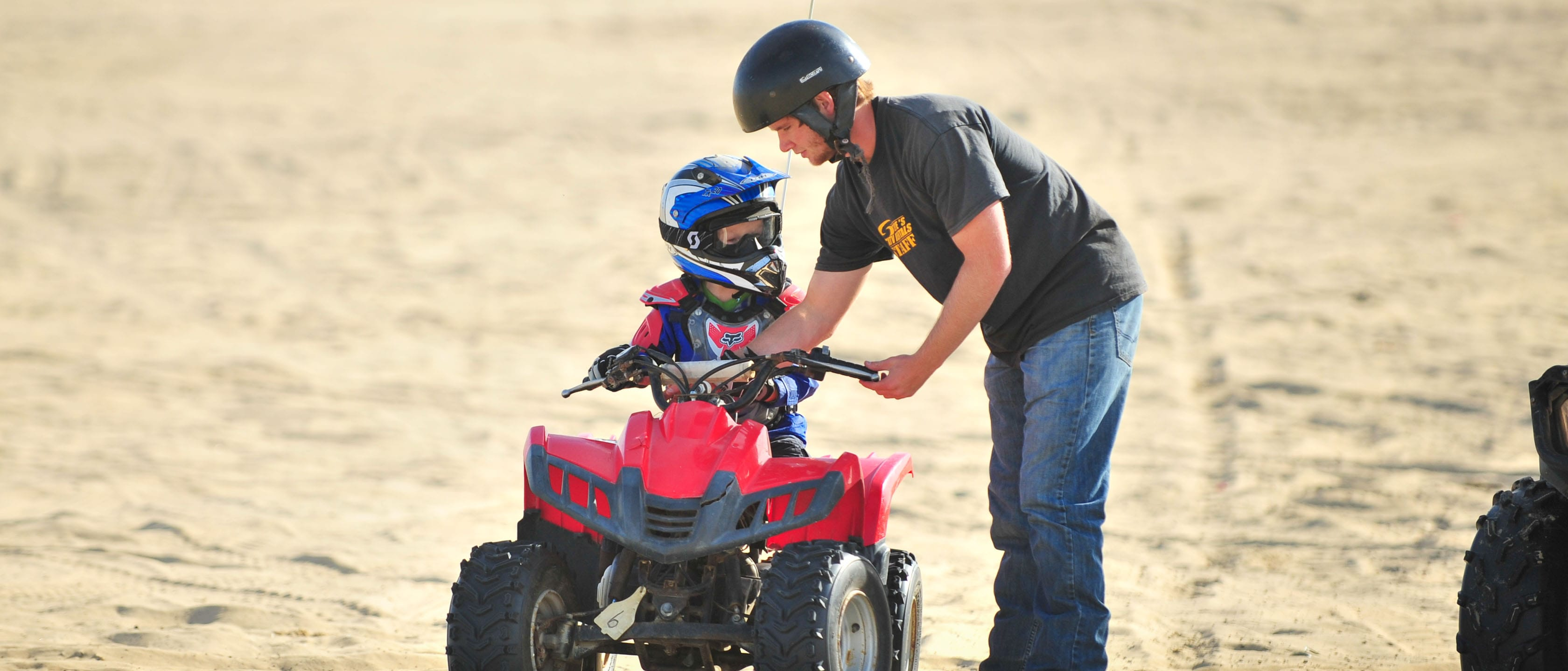 Adult teaching a child how to ride an ATV