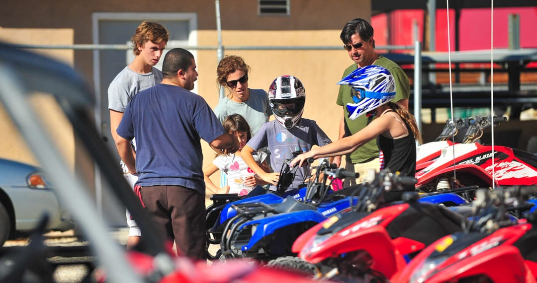 Family getting instruction about how to ride ATVs