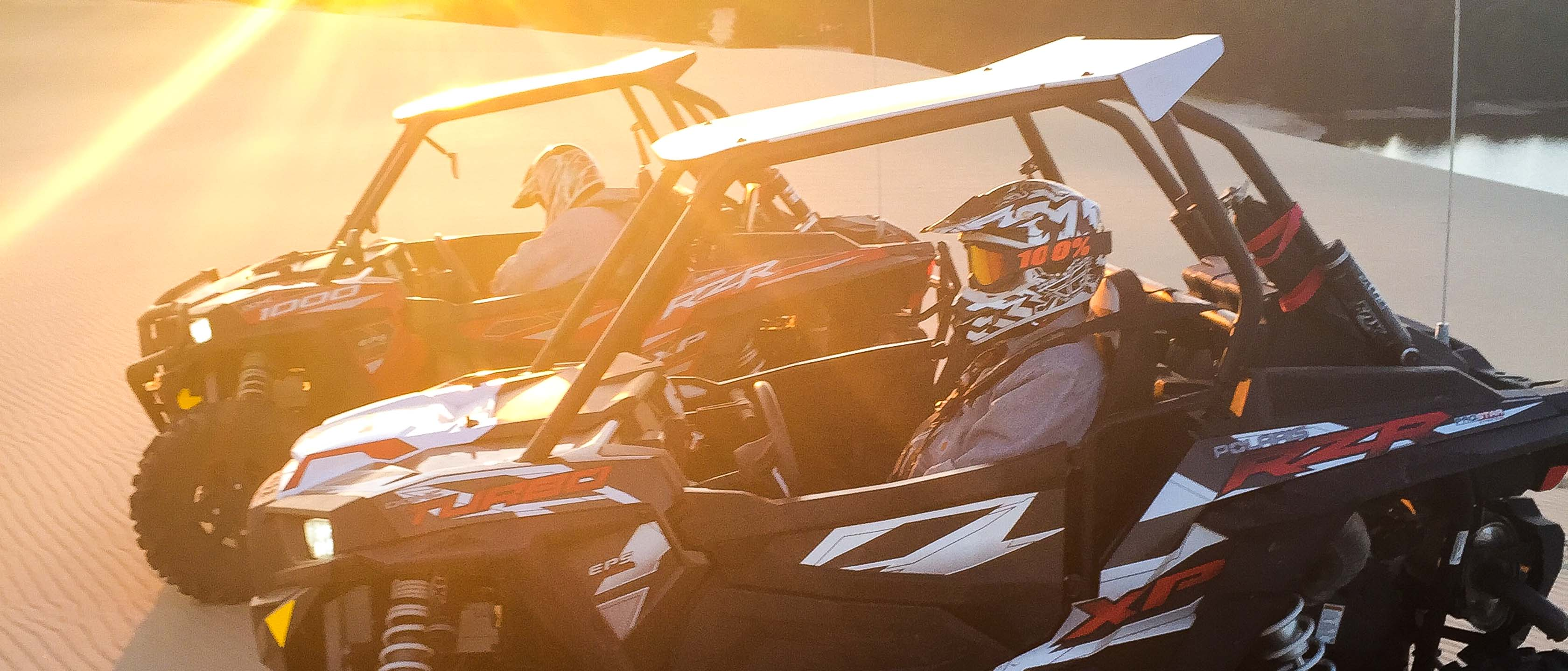 Two guests riding in Can Am Maverick Turbo at sunset