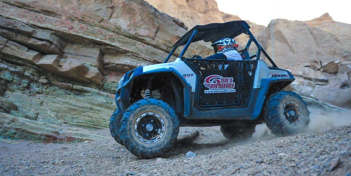 Guest riding RZR through rocky area in Palm Springs