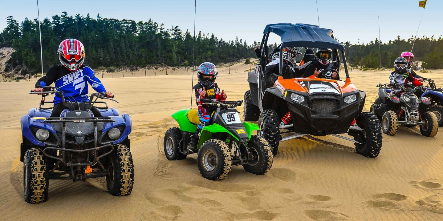 Children and adults, each on a different vehicle, at the Oregon Dunes location