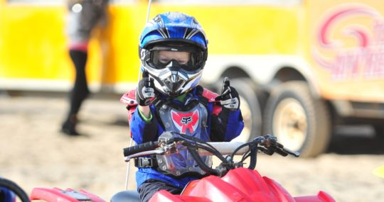 Young boy giving thumbs up on an ATV