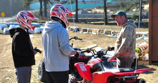 Two guests wearing helmets learning about ATVs