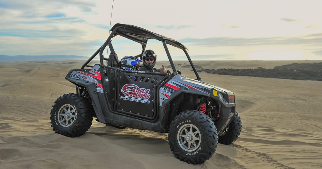 Guest giving the thumbs up while sitting in a Polaris RZR 800-2 in Pismo Beach