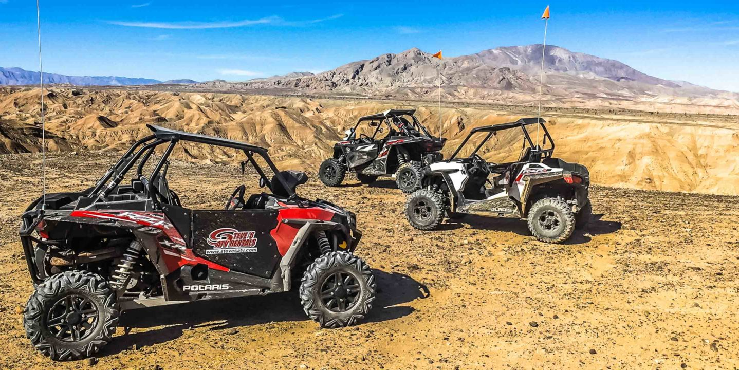 Three RZRs on rocky area in Palm Springs