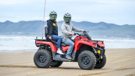 Two women riding an ATV by beach