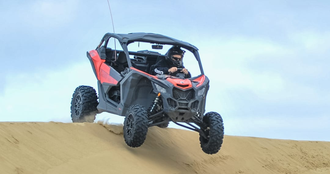 Guest riding on an ATV at Pismo Beach with front tires in the air
