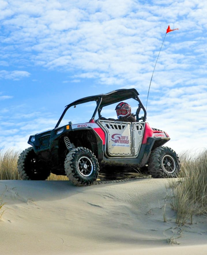 Guest riding Polaris RZR 800-4 through sand dunes in Oregon