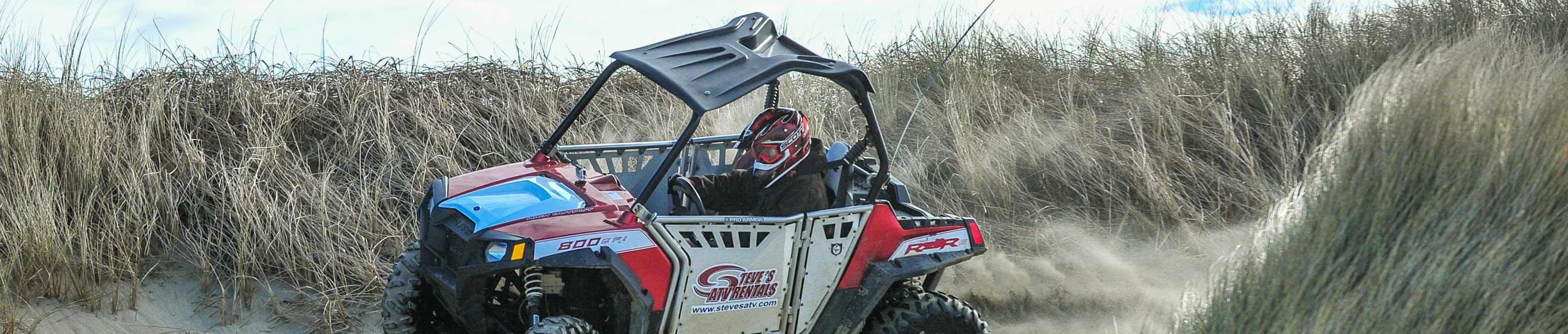 Guest riding a Polaris RZR 800-4 through grassy area
