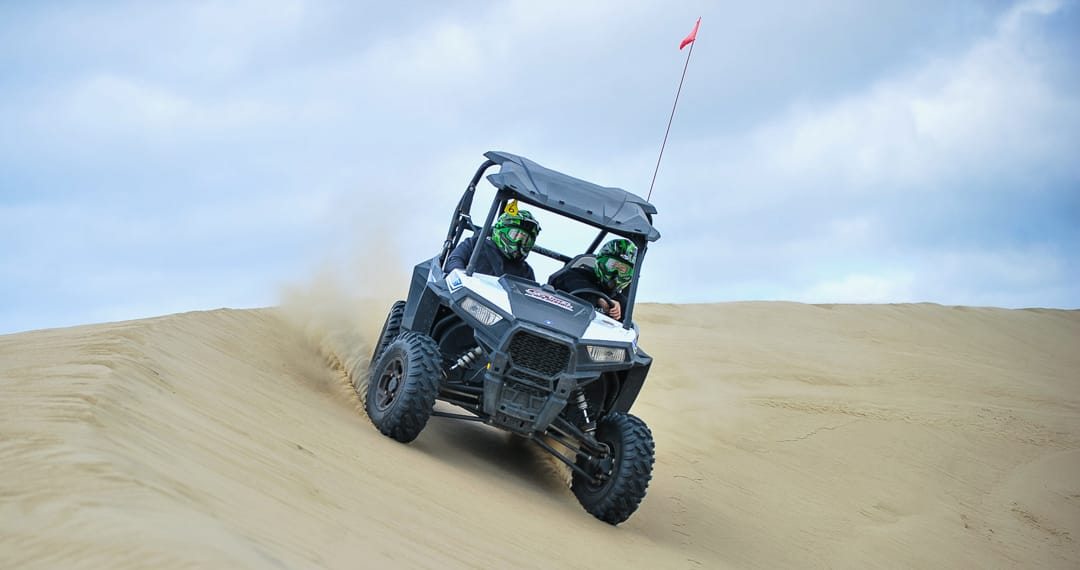 Two guests riding in Polaris RZR 900-2 on sand dunes
