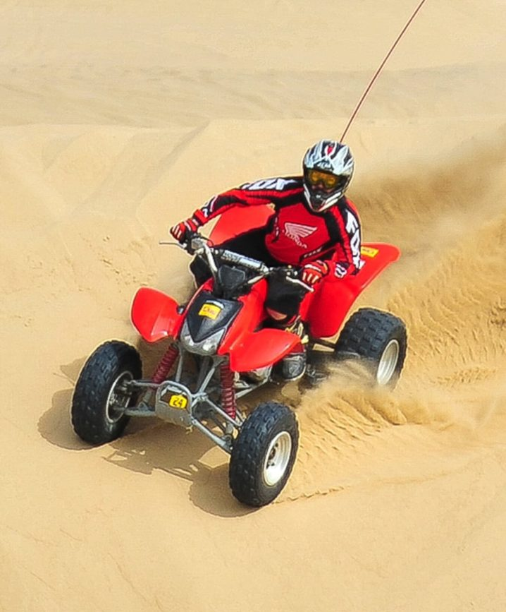 Guest riding ATV through sand dunes