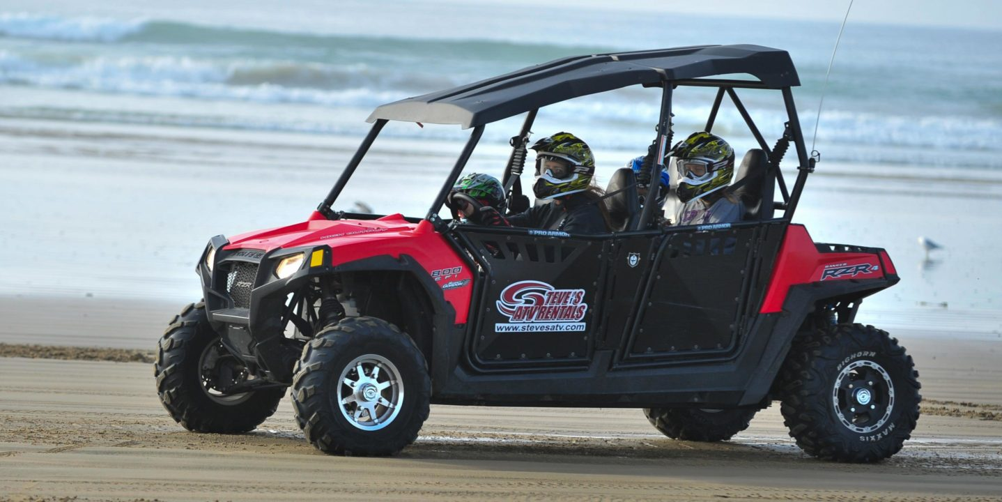 Guests riding in RZR on the beach