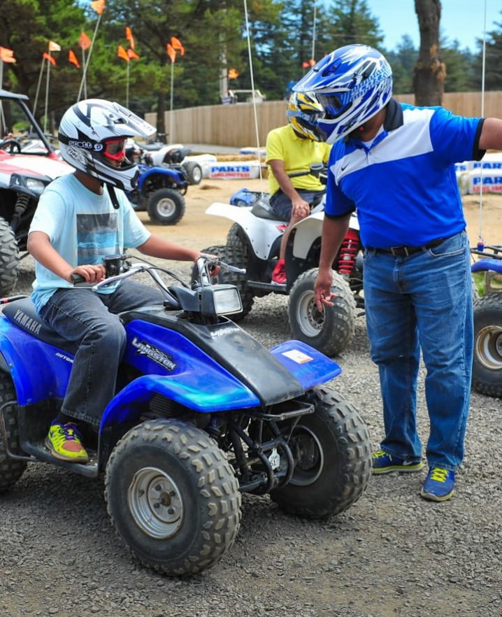 Adult talking to a child on an ATV, both wearing helmets.