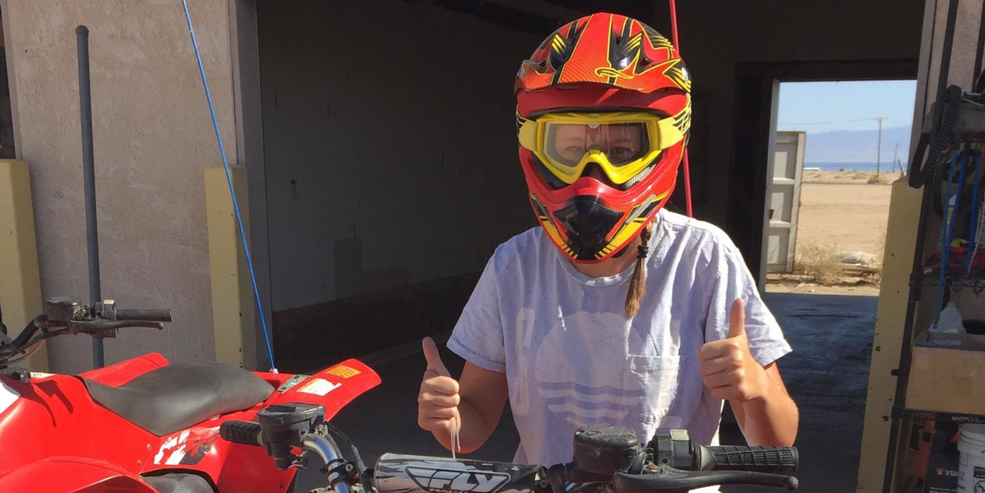 Girl wearing a red helmet and yellow goggles giving a thumbs up