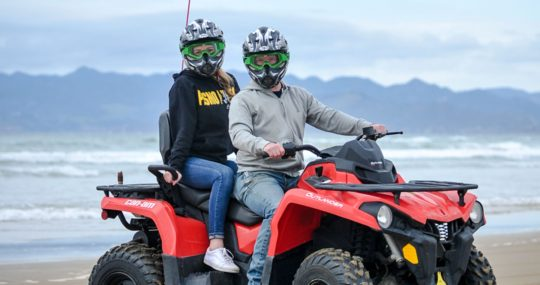 Two women sitting on an ATV at Pismo Beach