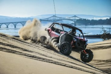 Riding an ATV through sand with a bridge in the background in Oregon