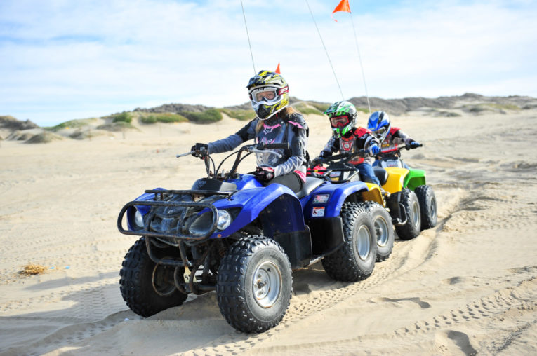 Family riding on colorful ATVs