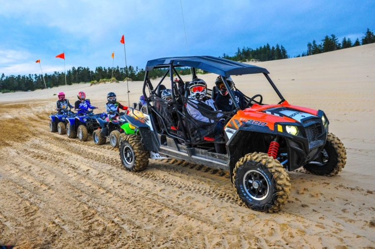 Family riding on different colored ATVs in Oregon