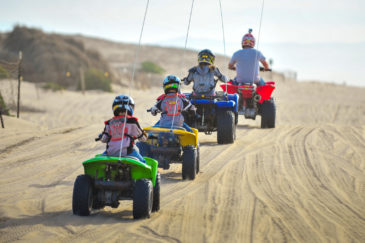 Family riding ATVs at Pismo Beach