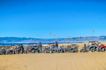 Steve ATV rental vehicles parked at Pismo Beach with guests standing nearby