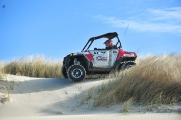 Guest riding a Polaris RZR 800-4 through grassy area