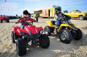 Two children sitting on ATVs at Pismo Beach