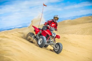 Male guest riding a rental through sand dunes