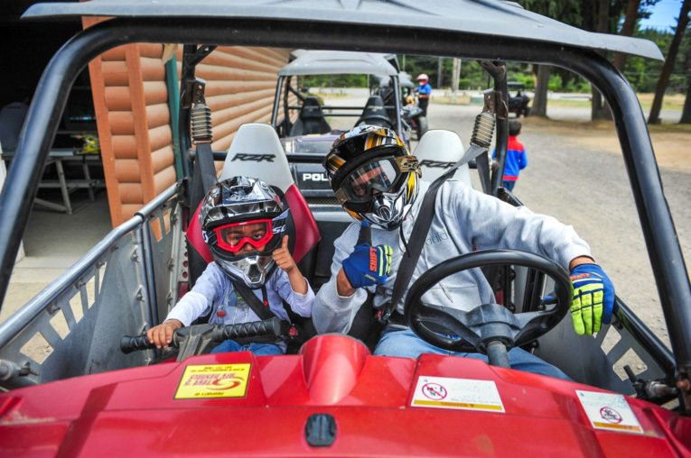Child and guest sitting in an ATV giving the thumbs up