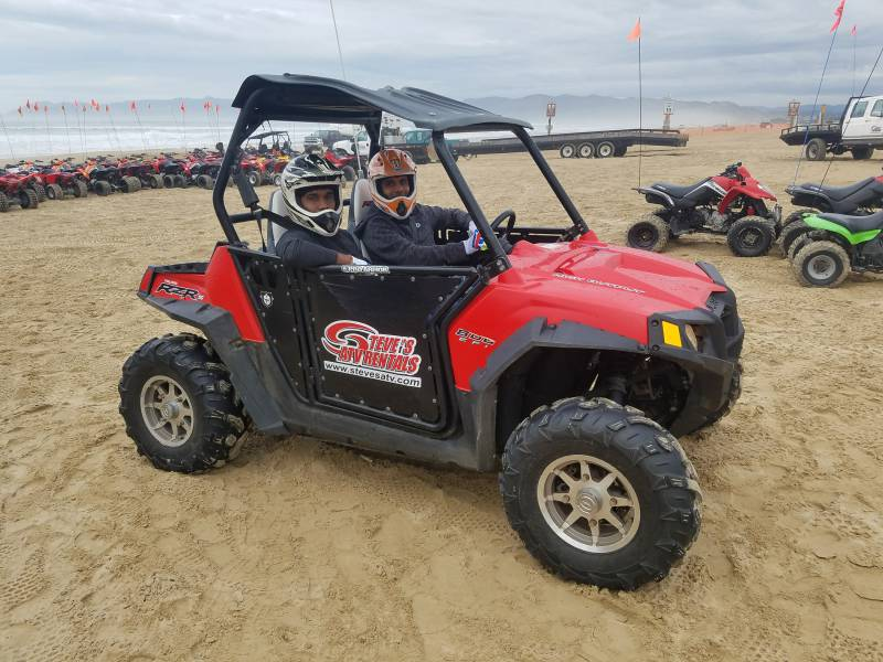 Guest riding a RZR on the beach